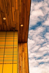 Image of a blue sky with clouds and a wooden yellow roof and wall with lights