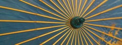 Image of a blue umbrella with yellow spokes that protects from the sun. 1930-1940 in Russia. Suitable as background, template, touristic guide, poster, greating card. Protection against sun concepts