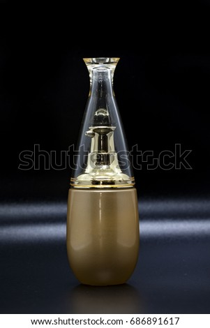Image of a bottle of golden perfume on a black background. #686891617