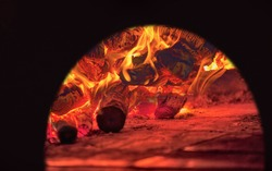 Image of a brick pizza oven with fire and flame
