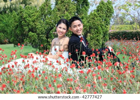Image of a bride and groom who is sitting out in the sun in the beautiful garden.