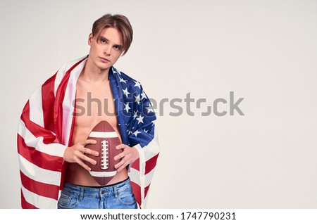 Photo of Image of a brutal young guy with blond hair and blue eyes, with a naked torso and an American flag on his shoulders, holding an American football ball in his hand. Copy space.