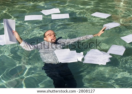Image of a business man drowning in paperwork.