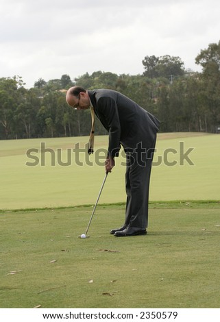 Image of a business man in a suit, about to putt out.