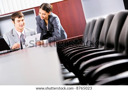 Image of a business man sitting and reading a document in the office with a smiling business lady standing near by