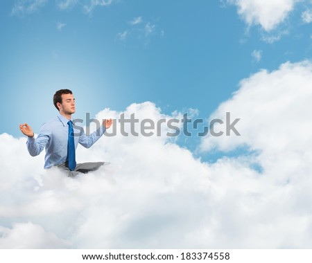 image of a businessman meditating on the clouds