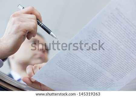Image of a businessman signing the contract viewed from below the transparent glass table