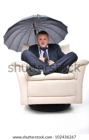 Image of a businessman sitting in comfortable armchair with an umbrella in his hand. Isolated on white background