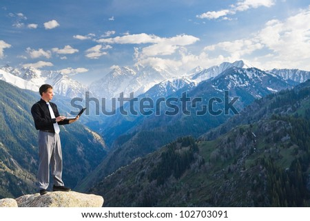 Image of a businessman standing on the top of the mountain, using a laptop. In the background a beautiful panorama of the valley with high peaks.