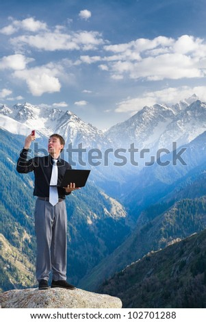 Image of a businessman standing on the top of the mountain, using a laptop, shouting because connection break. In the background a beautiful panorama of the valley with high peaks.