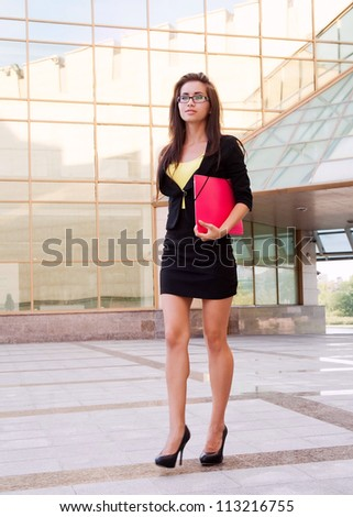 Image of a businesswoman standing near building