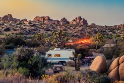 Image of a campground at Joshua tree national park during sunset with a RV or caravan placed
