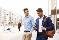 Image of a cheerful happy young two friends colleagues business men walking near business center talking with each other using mobile phone.