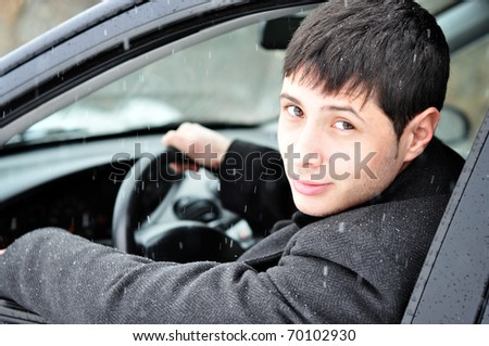 Image of a confident young businessman in his car