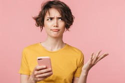 Image of a confused young beautiful woman posing isolated over pink wall background using mobile phone.