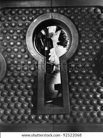 Image of a couple kissing viewed through a keyhole