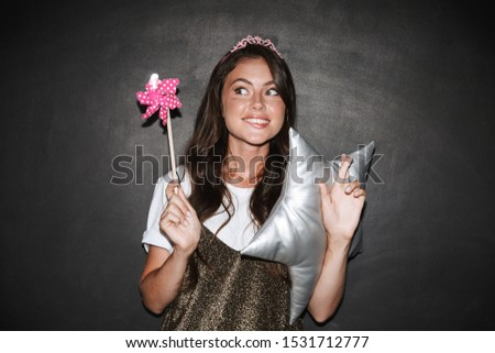 Image of a cute dreaming girl with pillow and toy magic wand isolated over chalkboard grey background make hopeful please gesture.