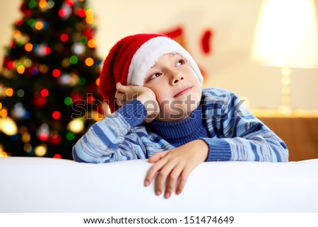 Image of a cute guy in a Santa hat dreaming of a new year�¢??s celebration
