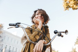 Image of a cute young amazing woman walking outdoors in park with bicycle beautiful spring day listening music.