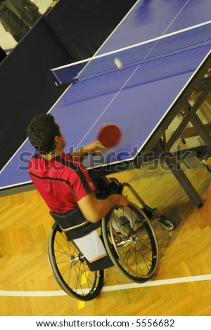 Image of a disabled man in wheelchair playing table tennis. Live image from an international tennis table competition for persons with disabilities.