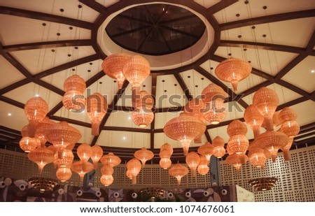 Image of a dome ceiling with wicker bamboo lamps at night.
