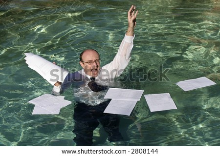 Image of a drowning business man with paperwork floating around him.