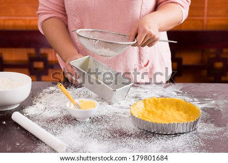 Image of a female baker sifting flour through a sieve for a baking on the foreground