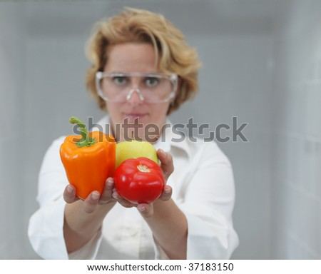 Image of a female researcher offering a tomato and an apple to suggest the idea that healthy eating is recommended also by scientists.Specific lighting for a classical research laboratory.