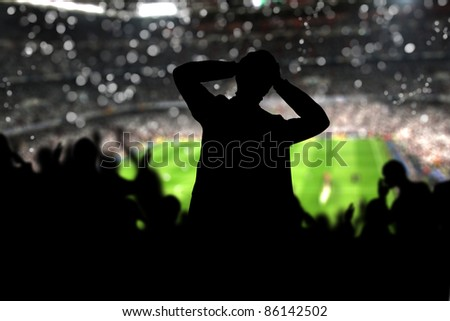 Image of a full stadium with silhouettes of fan on the foreground