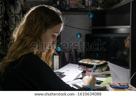 image of a girl doing school homework in the evening