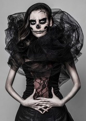 Image of a girl who is posing with a skull mask make up on the grey background