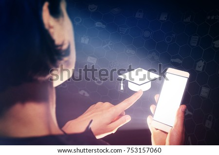 Image of a girl with a smartphone in hands. She presses on the graduation hat cap icon. Concept of online education, choose of career. #753157060