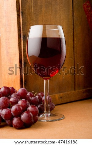 Image of a glass of wine and grapes next to wooden box