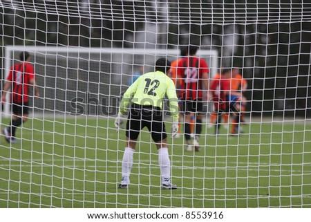 Image of a goalkeeper through the net, focus goalkeeper, rain all game