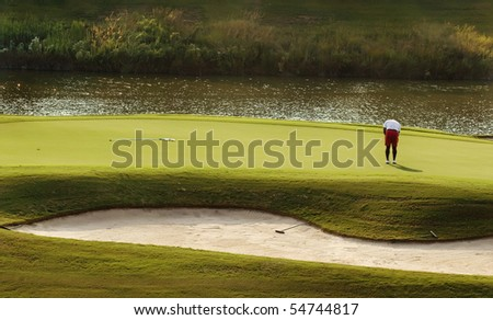 Image of a golfer putting on green