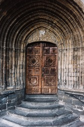 Image of a gothic chestnut wood door with geometric and floral carved decorations under a pointed arch with stone archivolts and a semicircular staircase.