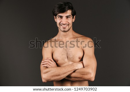 Image of a handsome naked young smiling man posing isolated over dark wall background.