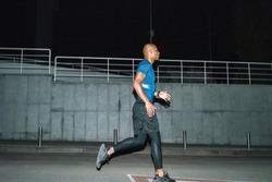 Image of a handsome strong african sports man runner at night outoors running.