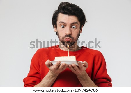 Image of a handsome young excited man posing isolated over white wall background holding birthday cake holidays.
