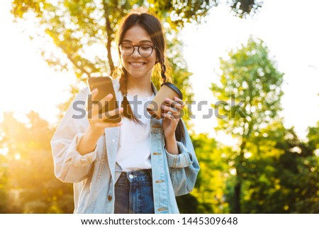 8cf0fee91bd9 Image of a happy cheery smiling young teenage girl student walking outdoors  in beautiful green park