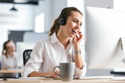 Image of a happy emotional business woman in office callcenter working with computer wearing headphones.