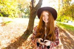 Image of a happy positive cutie young student redhead girl in autumn park using mobile phone.