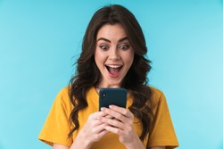 Image of a happy surprised shocked young pretty woman posing isolated over blue wall background using mobile phone.