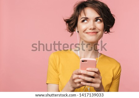 Image of a happy young beautiful woman posing isolated over pink wall background listening music with earphones using mobile phone. Сток-фото ©