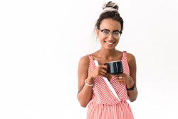 Image of a happy young cute cheery african woman with dreads posing isolated over white wall background drinking coffee or tea.