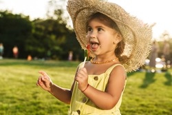 Image of a happy young cutie little girl eat lollipop candy outdoors in nature green park.