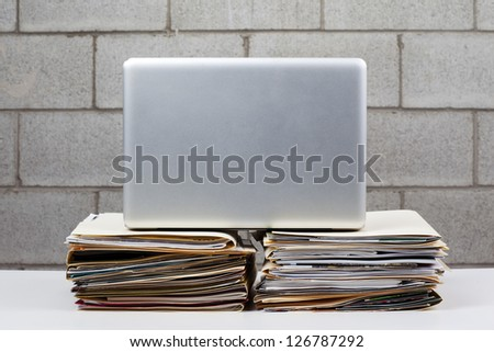 Image of a laptop kept on pile of folders against brick wall.