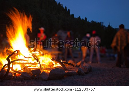 Image of a large campfire, around which people basking in the mountains at night