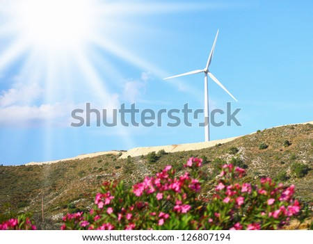 Image of a large windmill on the hill sunny day