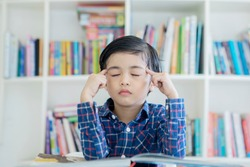 Image of a little boy thinking with eyes closed while learning in the library with bookshelf background